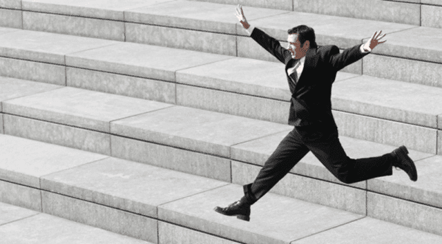 man jumping off steps in black suit and arms up in the air in joy