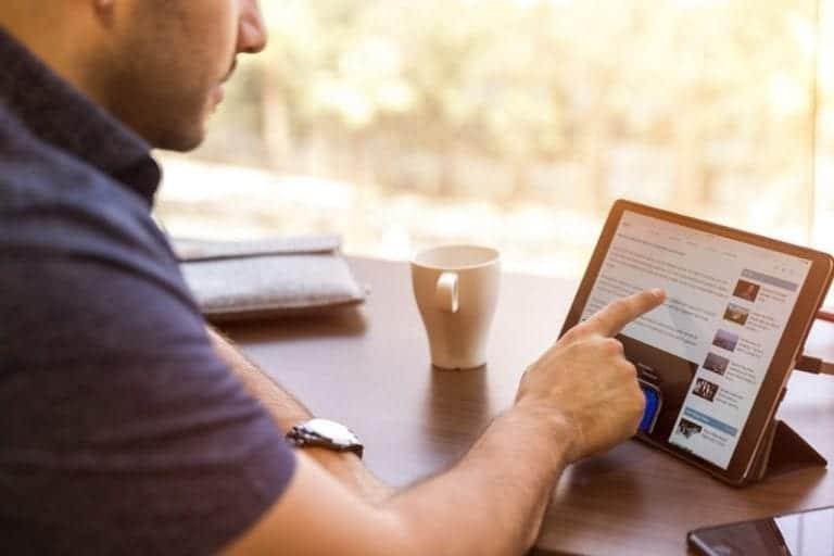 man scrolling through tablet